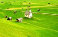 Rural landscape of tirol scenic view green fields in with scattered houses and old church austria Royalty Free Stock Photos