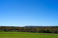 Rural Maine field with trees and distant windmills Royalty Free Stock Photo