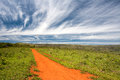 Rural orange dirt road with blue sky and far horizon Royalty Free Stock Photo
