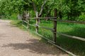 Rural path enclosed with lath fence at summer in park Stock Photos
