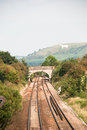 Rural railway track view of a countryside with a white horse in the background Stock Photo