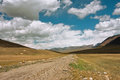 Rural road between the mountains of central asia with big clouds in the sky for a moment before a thunderstorm at sunny day Stock Photos