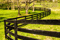 Rural scene with curving black fence dark wooden in setting of grass and bare trees Stock Images