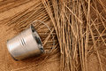 Rural still life metal bucket and a little straw on sackcloth background Stock Images