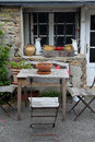 Rural table with pots and jugs wooden chairs Royalty Free Stock Photography
