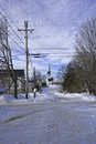 A rural view of new england snow covered roads with telephone and electric wires trees buildings and an old church in the distance Stock Images