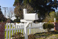 Rural white mailbox single sits in front of a picket fence Stock Photo