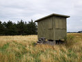 Rural wooden shed small house on the grass by the ocean Stock Images