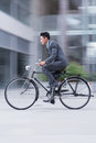 In a rush vertical image of an active young businessman on bike Royalty Free Stock Images