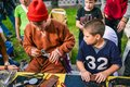 stock image of  Russia, city Moscow - September 6, 2014: The child observes the master, who makes leather goods. Master class for the