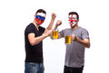 Russia and England football fans drink beer on white background.