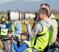 Photographer makes photo with modern digital camera and big telephoto lens on event outdoor Royalty Free Stock Photo