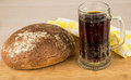 Russian brew in mug and bread loaf of wheat rye flour on wooden board Royalty Free Stock Photos