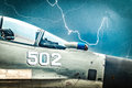 Russian fighter with gloomy sky background close up view of on of stormy bright lightning empty cockpit of military plane safety Royalty Free Stock Photos