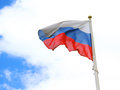 Russian flag tricolor. Blue sky with clouds background.