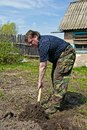 Russian granger digs up a garden bed Stock Image
