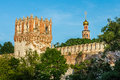 Russian monastery wall and tower with church spire in sunshine trees green sky Stock Images