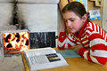 Russian schoolgirl reads textbook tver russia may sitting beside an open fire wood stove Royalty Free Stock Photo