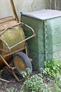 Rusted cangrejo and container for the composter and organic wast waste in a garden Stock Photography