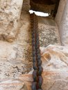 Rusted chain hanging on a stone wall Royalty Free Stock Photo