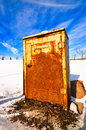 Rusted electrical box a rusty with snowy field and blue sky behind Stock Photo