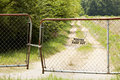 Rusted fence and gate on dirt road Royalty Free Stock Photo