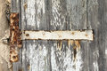 Rusted hinge on old door with flaking white paint Stock Image