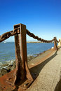 Rusted metal post and chain fence by bay Stock Images