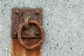 Rusted mooring ring on a concrete harbour wall Stock Image
