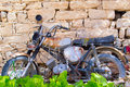 Rusted motorcycle very old against the stone wall Stock Images