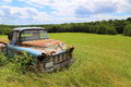 Rusted old truck in farm field sits abandoned a on a sunny day Stock Images