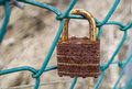 Rusted padlock on a fence green metal Royalty Free Stock Photos