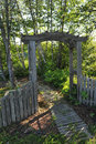 Rustic arbor this is a photo of a weathered natural cedar with a gate and walkwayscenic Stock Photo