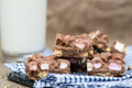 Rustic background with rocky road dessert squares with glass of on milk Royalty Free Stock Photo