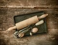 Rustic baking utensils with an old wooden rolling pin and manual egg beater lying on a metal tray with a fresh egg on an Stock Photo