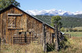 Rustic barn in southern colorado with snow capped mountains in the background Stock Photo