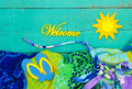 Rustic beach welcome sign yellow with sun on teal blue wooden background by towel sandals and tropical bikini border Stock Photos