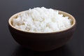 Rustic bowl of cooked white rice on dark surface Royalty Free Stock Photo