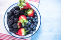 Rustic bowl full of forest summer berry fruits Royalty Free Stock Photo