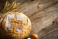 Rustic bread, golden wheat ears and fresh eggs on wooden background
