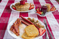 Rustic breakfast tasty pancakes bacon potatoes patties and fried eggs Stock Photos