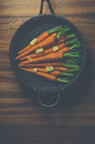 Rustic carrots in a pan on wood vintage style image of with butter and herbs Stock Photo
