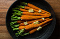 Rustic carrotts in a pan with butter on wood image of carrots and herbs Stock Photography