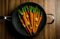 Rustic carrotts in a pan image of carrots on wood Royalty Free Stock Images