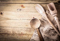 Rustic cooking utensils with a recipe wooden spoon ladle and scoop lying on folded cloth on it on an old cracked wooden Royalty Free Stock Photo