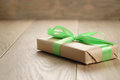 Rustic craft paper gift box with green ribbon bow on wood table Royalty Free Stock Photo