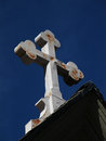 Rustic cross a white metal is displayed against a bright blue sky Stock Image