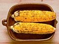 Rustic golden grilled corncob close up of a bowl of Stock Photos