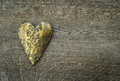 Rustic golden heart ornament on vintage wooden background Royalty Free Stock Photo