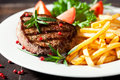 Rustic grilled steak with french fries Stock Images